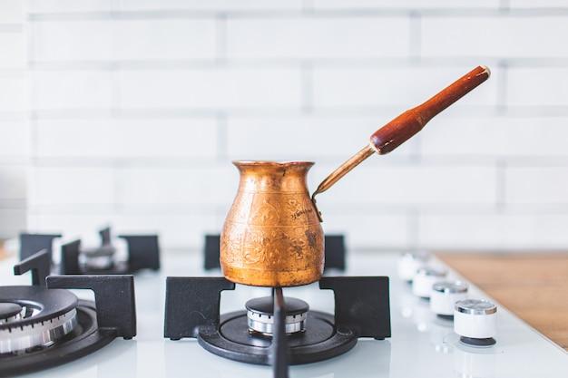 Oude koperturk met koffie die zich op een wit gasfornuis in een mooie lichte keuken bevinden. copyspace.