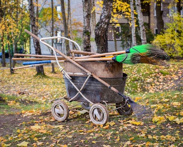 Oude kruiwagen en harken op de herfstaard
