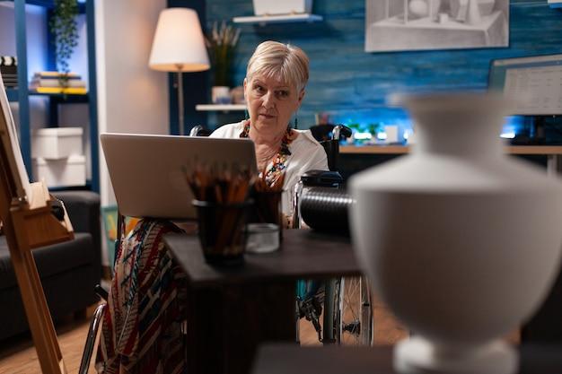 Oude kunstenaar met handicap die naar laptop in werkplaats kijkt