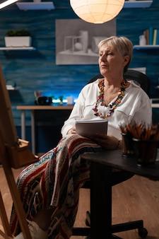 Oude kunstenaar zit in kunstwerkstudio met notitieboekje