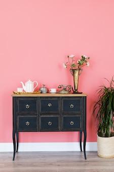 Oude ladenkast met voorwerpen op een roze muur.