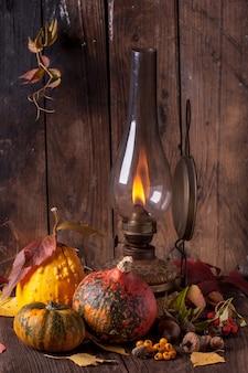 Oude lamp met pompoenen, eikels en bladeren