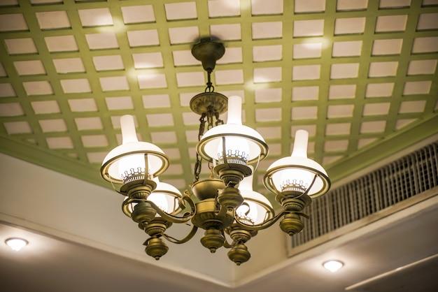 Oude lampen met glasstructuur op plafond in balzaal