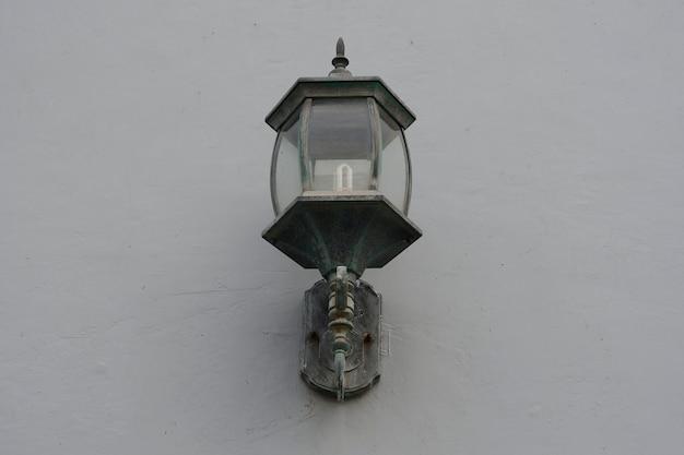 Oude lamplantaarn op de stenen muur, proces in vintage stijl.