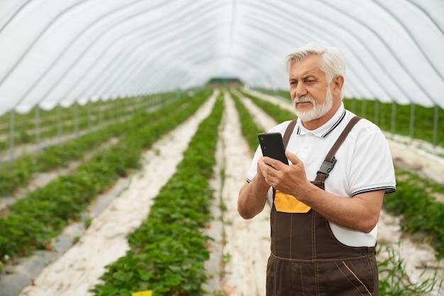 Oude landbouwer met smartphone in handen die zich bij serre bevinden