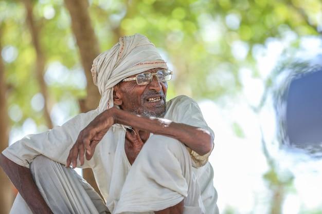 Oude landelijke indiase man zittend op de grond
