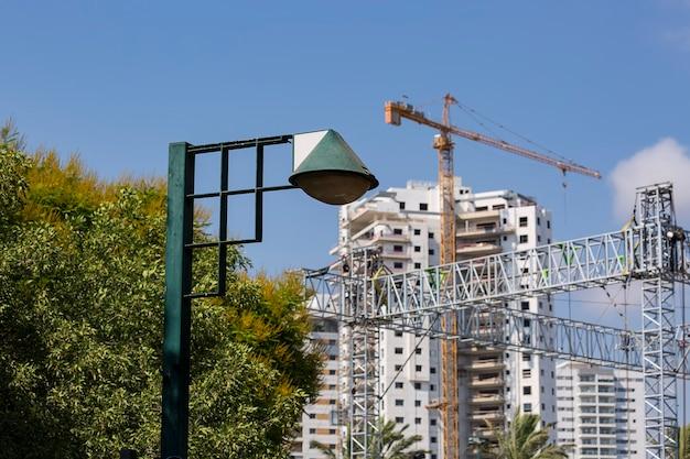 Oude lantaarn in het park met groene bomen, op de achtergrond in ondiepe scherptediepte. montagekraan bij bouw van flatgebouw, blauwe de lentehemel. vastgoed ontwikkeling