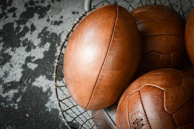 Oude lederen ballen op metalen emmer