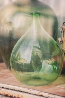 Oude lege wijnflessen achter het glas