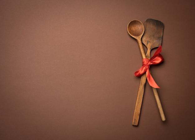 Oude lepel en spatel gebonden met rood lint op een bruine achtergrond, bovenaanzicht, kopieer ruimte