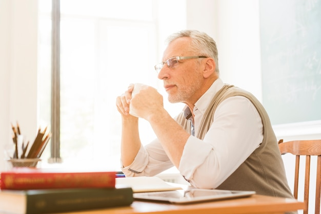 Oude leraar die in klaslokaal drinkt