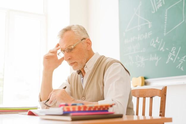Oude leraar die thuiswerk in klaslokaal controleert