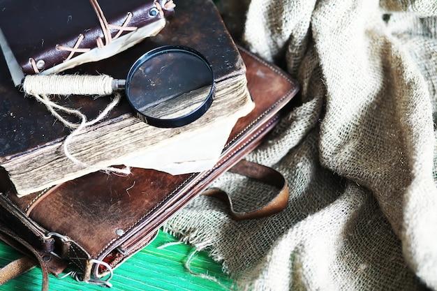 Oude leren tas met een vergrootglas op de achtergrond van een bruine reiziger houten tafel met kopieerruimte.