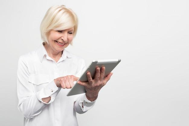 Oude maar gelukkige vrouw gebruikt een gloednieuwe tablet. ze test het omdat ze van nieuwe technologieën houdt.