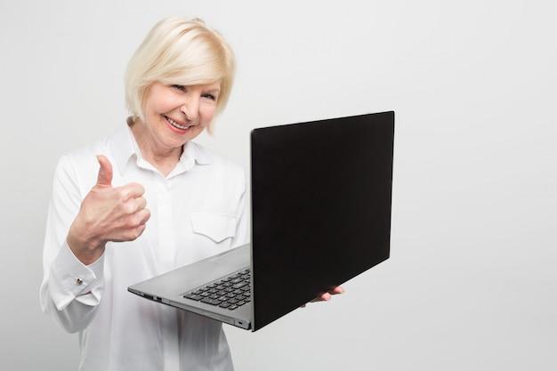 Oude maar moderne vrouw houdt een nieuwe laptop. ze gebruikt het graag. de dame wil het liefst alles weten over nieuwe technologieën en het laatste nieuws over computerapparatuur.