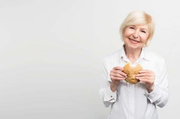 Oude maar tevreden vrouw houdt een hamburger in haar handen. ze heeft net een hap genomen. deze dame houdt van de smaak van deze maaltijd. soms eet ze graag junkfood.
