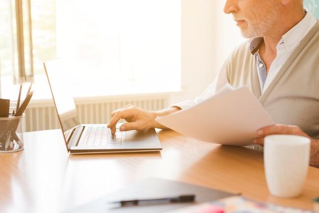 Oude man aan het werk op laptop