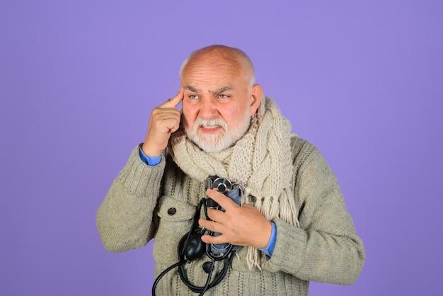 Oude man arteriële bloeddruk gezondheidszorg bloeddrukmeter ernstige hoofdpijn gezondheidszorg concept