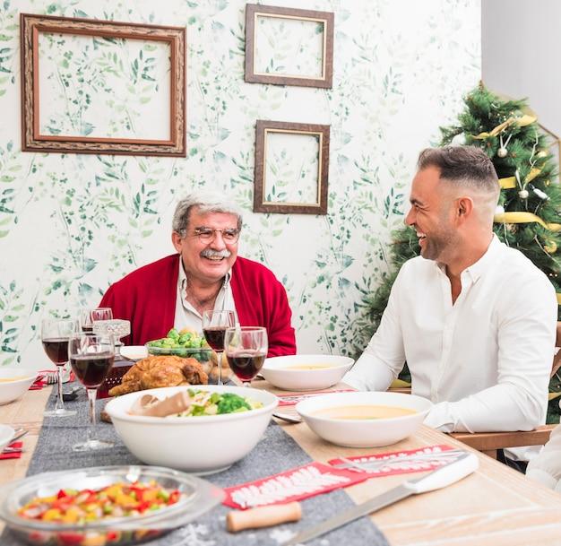 Oude man die aan zoon bij feestelijke lijst spreekt