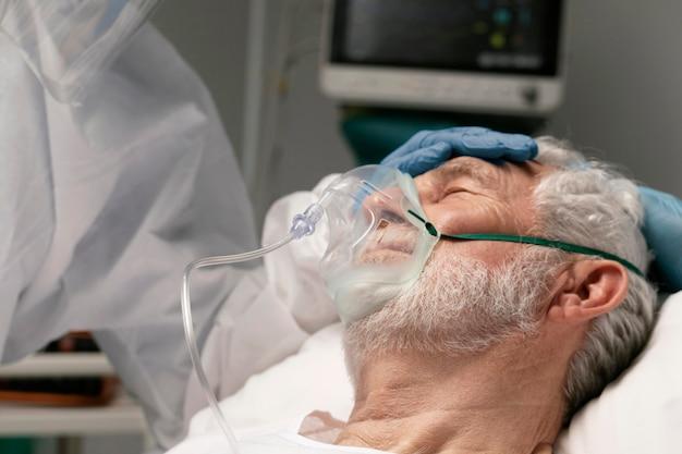 Oude man die ademt met een speciale uitrusting