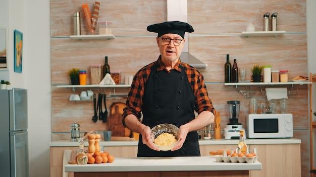 Oude man die bonete draagt terwijl hij het recept voor voedselbereiding uitlegt terwijl hij naar de camera kijkt. gepensioneerde blogger-chef-beïnvloeder die internettechnologie gebruikt om op sociale media te communiceren met digitale apparatuur