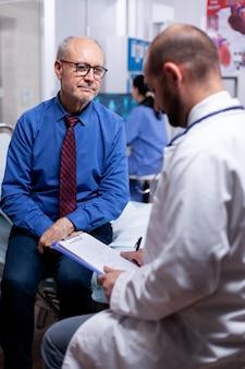 Oude man die de vragenlijst van de arts beantwoordt tijdens onderzoek in de ziekenhuiskamer