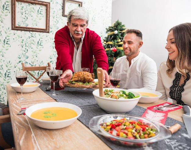 Oude man die gebakken kip op kerst tafel zetten
