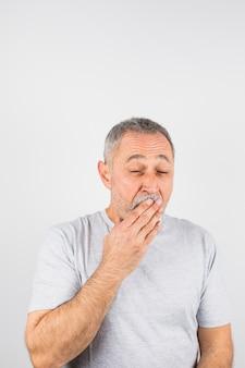 Oude man die geeuwend zijn mond bedekt