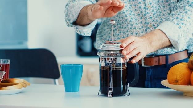 Oude man die het deksel van de franse pers naar beneden duwt terwijl hij koffie maakt voor het ontbijt in de keuken. bejaarde die 's ochtends geniet van vers bruin café-espressokopje cafeïne uit vintage mok, filter relax