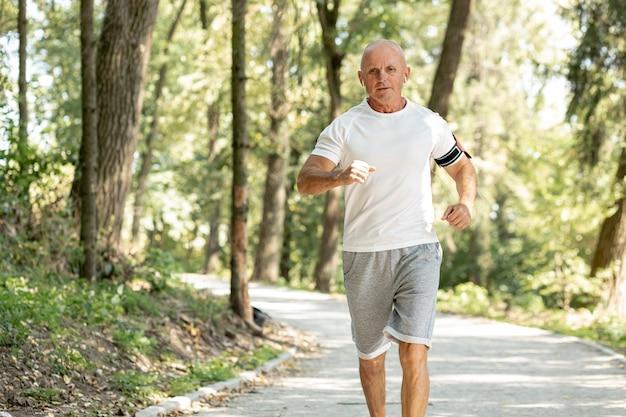 Oude man die in het bos loopt