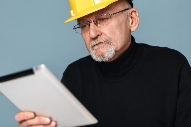 Oude man die in veiligheidshelm op tablet kijkt