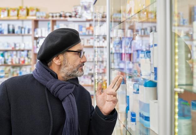 Oude man die medicijnen in drogisterij kiest.