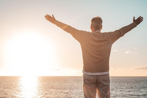 Oude man die met open armen naar de zonsondergang en de zee kijkt en zich vrij en gelukkig voelt - vrijheid en geluk voelen levensstijl en concept