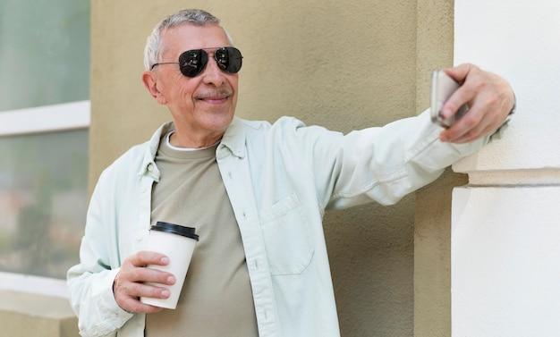 Oude man die selfie maakt met telefoon