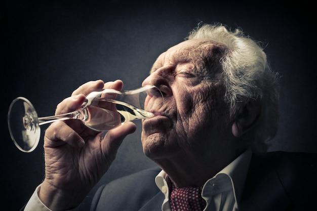 Oude man die wijn drinkt