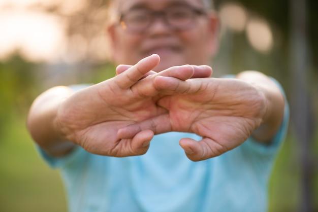 Oude man die zich uitstrekt arm vóór outdoor oefening in een park tijdens zonsopgang