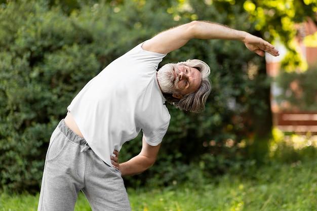 Oude man die zich uitstrekt in de natuur