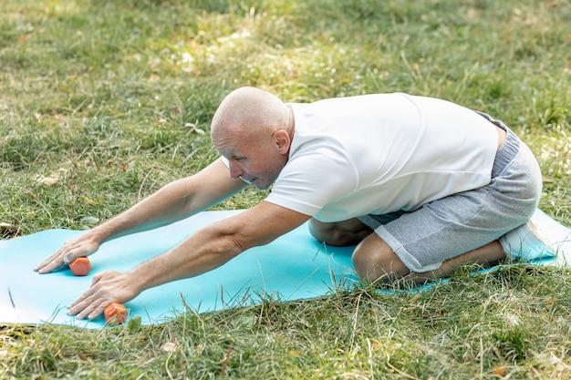Oude man die zich uitstrekt over yoga mat