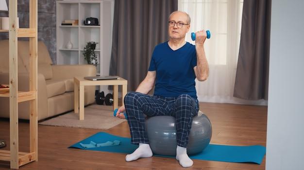 Oude man doet biceps training met halters op stabiliteitsbal. bejaarde gepensioneerde gezonde opleiding gezondheidszorg sport thuis, fitness activiteit uitoefenen op oudere leeftijd