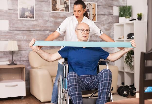 Oude man doet spierblessure oefening met behulp van weerstandsband met verpleegster ernaast