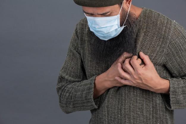 Oude man draagt masker terwijl hij voelt dat pijn op de borst niet goed is