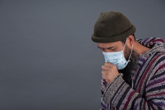 Oude man draagt masker terwijl hoesten op grijze muur.