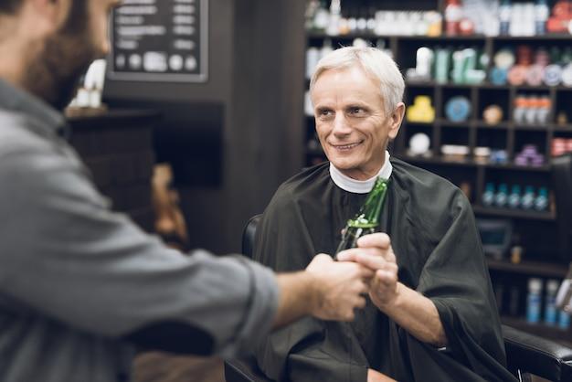 Oude man drinkt alcohol in de stoel van de kapper in kapperszaak,
