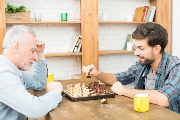 Oude man en jonge kerel schaken aan tafel in de kamer