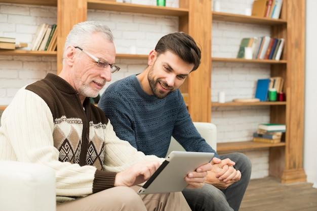 Oude man en jonge lachende man met behulp van de tablet op de bank