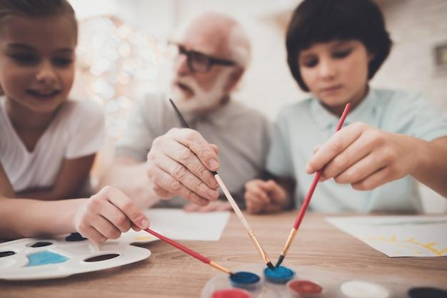Oude man en kinderen houden borstels samen schilderen.