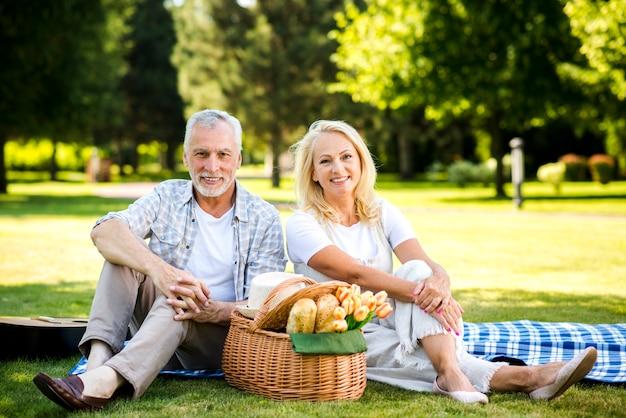 Oude man en vrouw die camera bekijken
