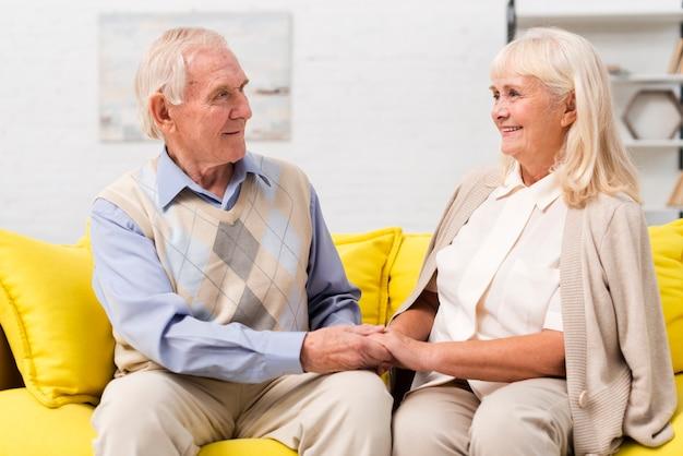Oude man en vrouw die op gele bank spreken