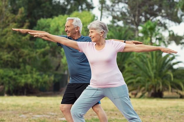 Oude man en vrouw die uitrekkende oefening doen