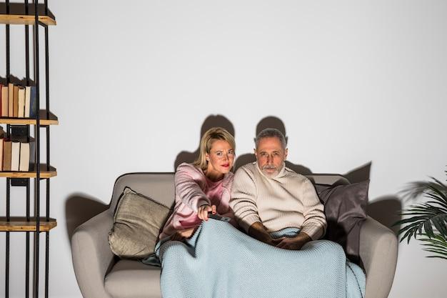 Oude man en vrouw met afstandsbediening van de televisie veranderende kanalen en tv kijken op de bank